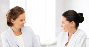 picture of two businesswomen having discussion in office about dresscode